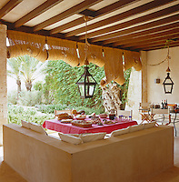 An L-shaped sofa in the outdoor dining room is made of stucco, the lanterns are from India and the room is sheltered from the sun by grass blinds