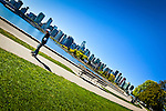 A skater blurs by on a trail in Stanley Park, Vancouver, B.C, Canada on a sunny day, early summer. Downtown skyline fills the background.