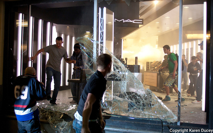 Rioters break windows and run through a store in downtown Vancouver,BC on June 15, 2011. (photo copyright Karen Ducey)