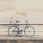 a mans black bicycle leans against a stone wall in cambridge, england