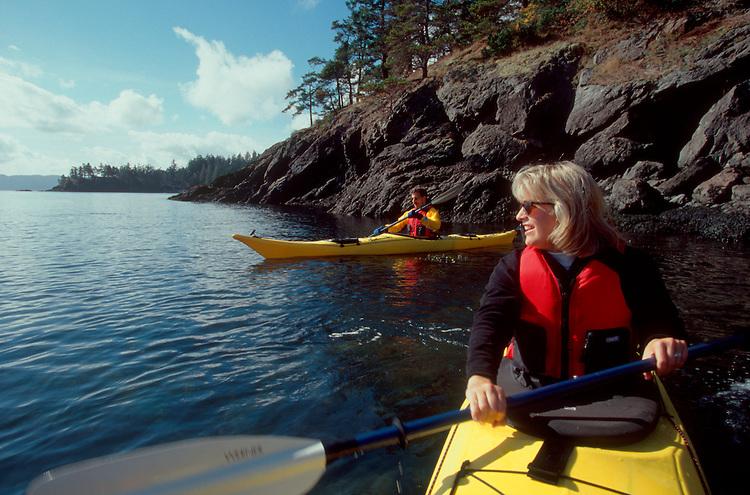 San Juan Islands, Sea kayaking couple off Orcas Island, Washington State, Pacific Northwest, USA,.