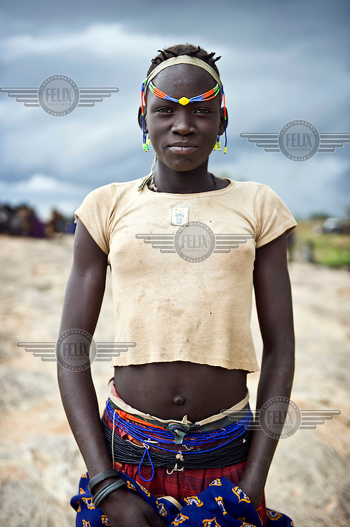 A portrait of 13 year old Maritina Mawot from the Karamojong community wearing traditional clothing and decoration.