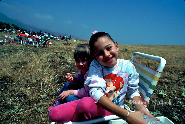 Two girls witting on beach chair in a field