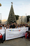 Palestinian Christian children take part at the ninth annual Christmas march past a Christmas tree at the Manger Square near the Church of the Nativity, revered as the site of Jesus Christ's birth, on December 22, 2016 in the biblical West Bank town of Bethlehem. Photo by Wisam Hashlamoun