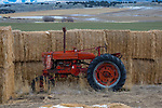 Idaho, Southeast, Aberdeen. A old red tractor by hay bales in mid winter.