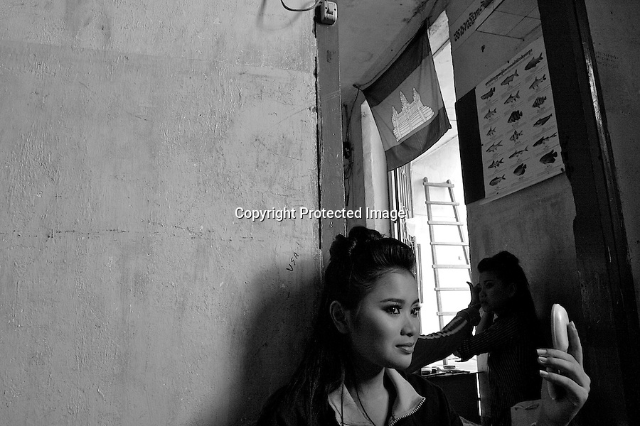 Children of Bassac. Duong Darapenh, nickname Sreypenh, is checking her make up in a small mirror, sat on the floor. SreyPenh is a charismatic dancer of the troup. Phnom Penh, Cambodia - 2007