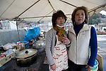 Sisters Hiroko Niinuma, 57 (l) and Miyoko Sasaki, 59, stand by the makeshift kitchen where they make meals for refugees outside Senjuin temple in the historic city of Kamaishi, Iwate Prefecture, Japan on 04 April, 2011. .Photographer: Robert Gilhooly