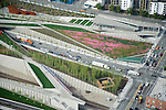 Aerial view looking northeast at Seattle's Olympic Sculpture Park.  Richard Serra's 'Wake' is the 5-piece sculpture at top left,  and Tony Smith's 'Stinger' is visible in lower right.  Elliott Avenue, a major thoroughfare, runs underneath the park as native summer wildflowers bloom in the meadow areas overhead.