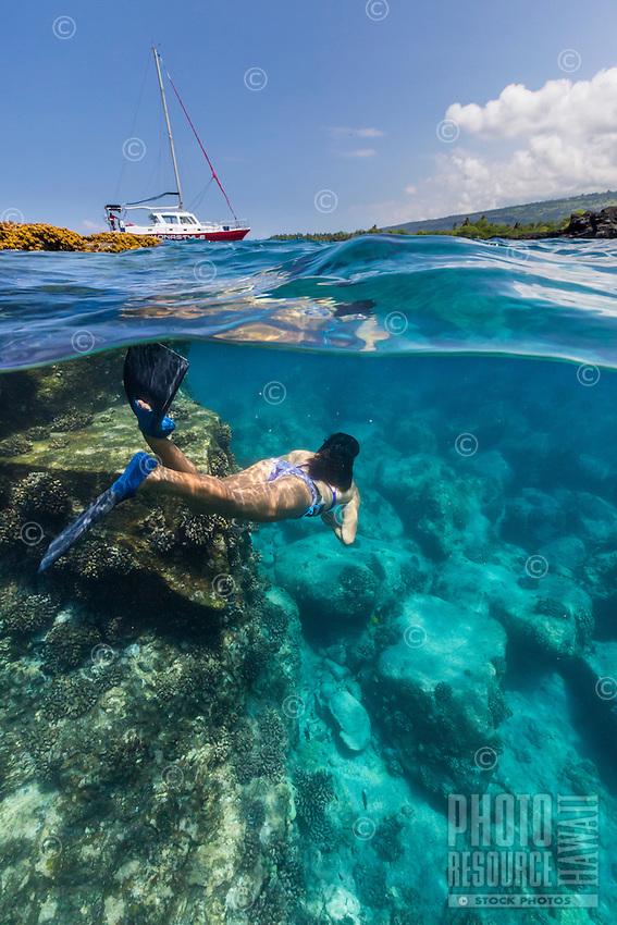 A woman snorkels in clear water off the Kona coast of the Big Island. (Note: The swimmer is model released, the man in the far distance currently is not.)