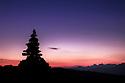Stone cairn on mountain summit at dawn, Nordtirol, Tirol, Austrian Alps, Austria, July.