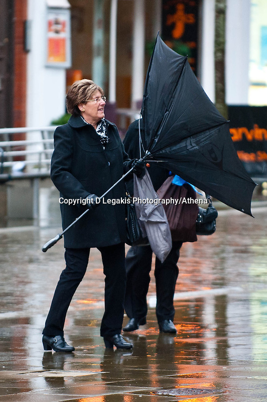 Wednesday 12 February 2014<br /> Pictured: A woman struggles in the wind with a broken umbrella<br /> Re: People struggle with the high winds in the center of Swansea. The met office has today issued more warnings of extreme weather over the next few days.