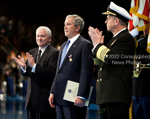 Arlington, VA - January 6, 2009 -- United States President George W. Bush, center, is applauded by Robert Gates, Secretary of Defense, left, and Admiral Michael Mullens, Chairman of the Joint Chiefs of Staff, after he was awarded the Department of Defense Medal for Distinguished Public Service during the Military Appreciation Parade at Fort Myer in Arlington, Virginia, U.S. on Tuesday, January 6, 2009.        .Credit: Joshua Roberts - Pool via CNP