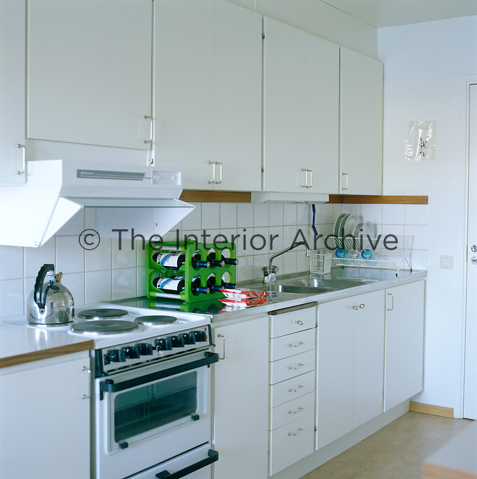 In this cool and tranquil all-white and stainless steel kitchen a vivid note of colour comes from a funky apple-green plastic wine rack