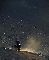 Horseback riders kicking up dust in HALEAKALA NATIONAL PARK on Maui in Hawaii USA