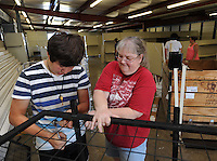 NWA Democrat-Gazette/ANDY SHUPE<br /> Joaquin Martinez, 16, (left) a volunteer from Farmington, and Martha Brown of the Goshen Extension Homemakers Club work together Friday, Aug. 14, 2015, to assemble a rack to be used to hold hanging plants in the adult exhibit hall at the Washington County Fairgrounds in Fayetteville. Organizers plan a work day Aug. 22 for the fair which begins Sept. 1.