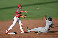 Clearwater Threshers second baseman KC Serna (8) turns a double play as Michael Garza (21) slides in during a game against the Brevard County Manatees on June 28, 2014 at Bright House Field in Clearwater, Florida.  Brevard County defeated Clearwater 6-4.  (Mike Janes/Four Seam Images)