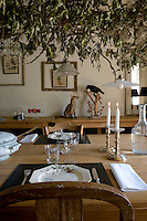 In the kitchen a romantic arrangement of dried wild clematis is suspended over mis-matched china on the antique dining table whilst on the adjacent console table a fable from Aesop is re-enacted by a stuffed fox and crow