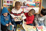 Preschool Headstart New York City 3 year olds parallel play group of 4 boys all looking at books horizontal