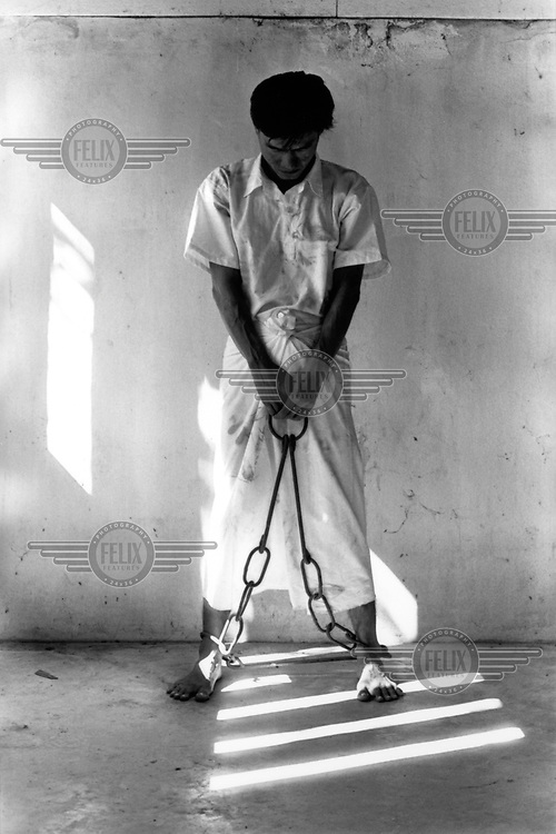 Former Burmese political prisoner Ye Htun Oo poses in regulation prison uniform and shackles. This is the position adopted when prison officers address the prisoner.