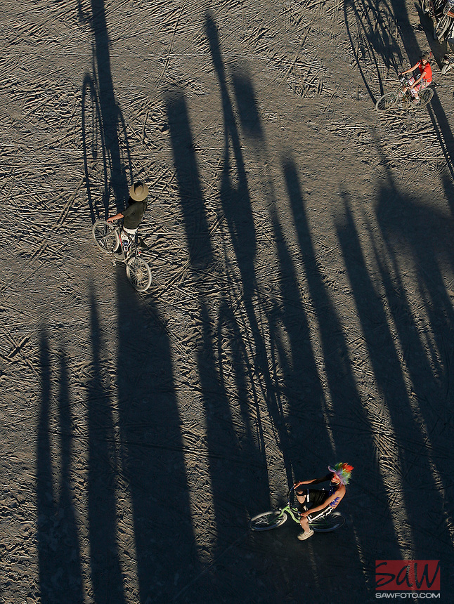 BLACK ROCK CITY,NV - AUGUST 28,2008:  Cyclist at Burning Man makes his way past shadows as the sun sets, August 28,2008.