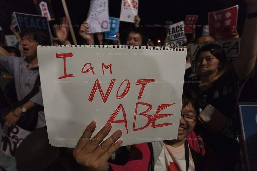 "A young Japanese protestor holds a sign that says ""I am not Abe"" as he takes  part in a protest rally by SEALD activists outside the Japanese Diet building, Nagatacho, Tokyo, Japan. Friday July 10th 2015 SEALD (Student Emergency Action for Liberal Democracy) is a student activist group that is against the neoliberal policies and nationalist agenda of Japanese Prime Minister, Shinzo Abe."