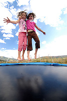 Two young girls bouncing on a trampoline, Steamboat CO