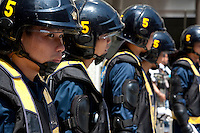 Policemen in riot gear line up in a street near Yasukuni Shrine. On August 15th every year people gather at Yasukuni Shrine to commemorate the end of the Pacific War. Notionally a call for remembrance and continued peace it is also a Mecca for right wing nationalist including  the paramilitary Uyoku Dantai. Tokyo, Japan, August 15th 2009