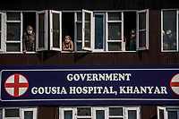 Masked relatives of patients look out from the windows of the Khaniyar hospital. The first positive case of coronavirus was identified in the Khaniyar area the previous night leading the local government to impose section 144 in Kashmir to stop spread of Coronavirus.<br /><br />Section 144 of the criminal code '...prohibits the assembly of four or more people in an area...'