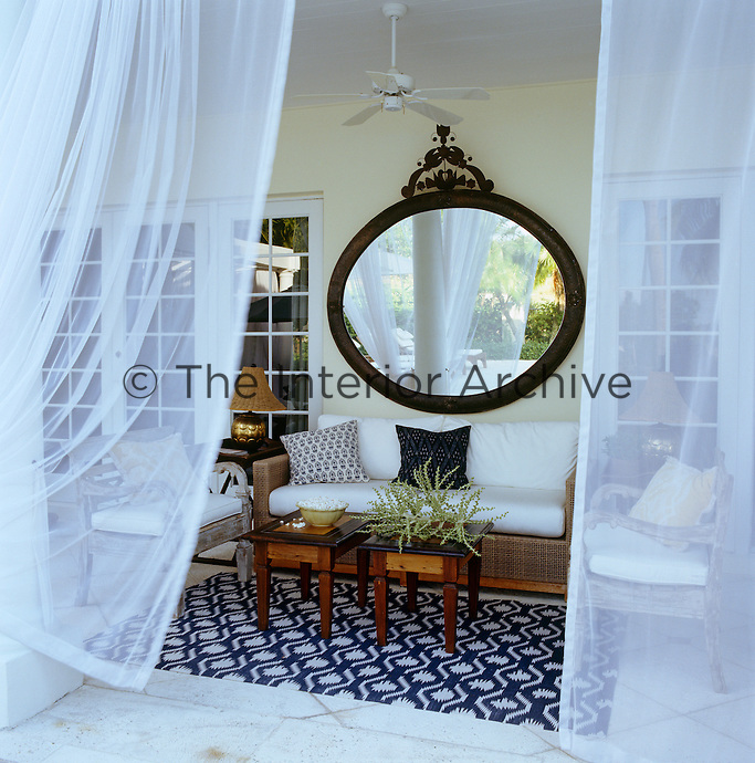 The cool covered terrace is furnished with a cane sofa and a pair of antique armchairs and is shielded from the hot Florida sun by sheer white curtains on all sides