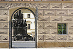 The open gate of Schwarzenbersky Palace, looking out onto a plaza with statues at the Prague Castle in Prague, Czech Republic.