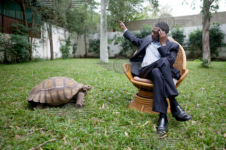 Musician Youssou N'Dour with a pet giant tortoise in the garden at his home in Dakar.