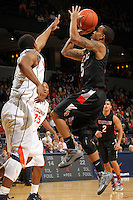 Dec. 22, 2010; Charlottesville, VA, USA; Seattle Redhawks guard Cervante Burrell (5) shoots in front of Virginia Cavaliers forward Akil Mitchell (25) and Virginia Cavaliers guard Jontel Evans (1) during the game at the John Paul Jones Arena. Mandatory Credit: Andrew Shurtleff