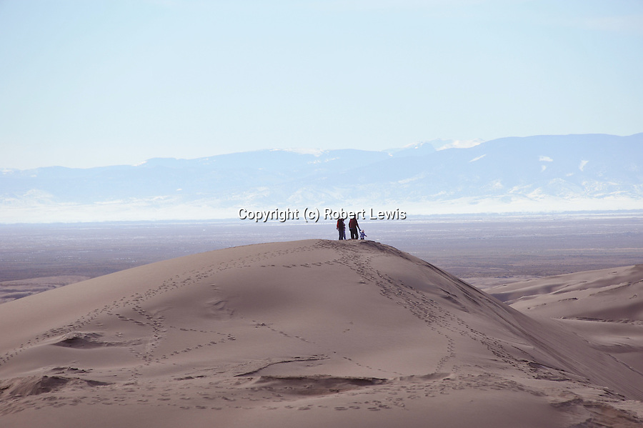 three hikers against the western mountains from a sand dune.