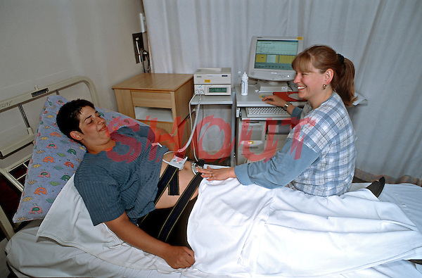 Midwife talking to pregnant woman linked up to a Dawes Redman monitor which is used to provide a trace for the babys heart rate. The examination is taking place on an almost full term pregnant mother to be. This image may only be used to portray the subject in a positive manner..©shoutpictures.com..john@shoutpictures.com