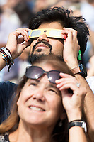 People gather to observe the solar eclipse in the Kresge Oval and outside the Stratton Student Center at MIT in Cambridge, Massachusetts, USA, on Mon., Aug. 21, 2017. This solar eclipse is the first in nearly 40 years to have a path observable total eclipse from coast to coast in the United States. People at this location in Massachusetts, however, only observed about 66% coverage of the moon over the sun. MIT set up telescopes to safely observe the eclipse, in addition to homemade camera obscura and pinhole viewers and eclipse glasses.