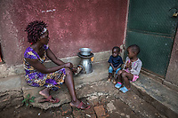Uganda, Hoima. Irene Ahebwa (26), sells fruits and vegetables and has a son, Benjamin. At home she uses a BioLite cook stove that charges a light and mobile phone. With Angel Naluwaga (6), family friend.