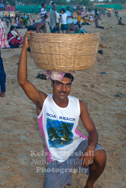 A local Indian man carrying a basket of fruit on his head stops and poses for the camera. Calangute beach, Goa - Southern India.