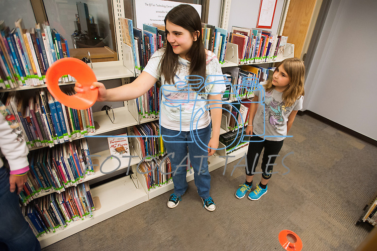 Katie Tubiello, left, and Sandra Tubiello look for course ideas during the Mini Golf Night at the Carson City Library on Friday, May 9, 2014. Kids and parents built a custom mini golf course throughout the library using anything at their disposal and engineering ideas to make a difficult course. Everything from tables to shelves were used to create creative courses.<br />