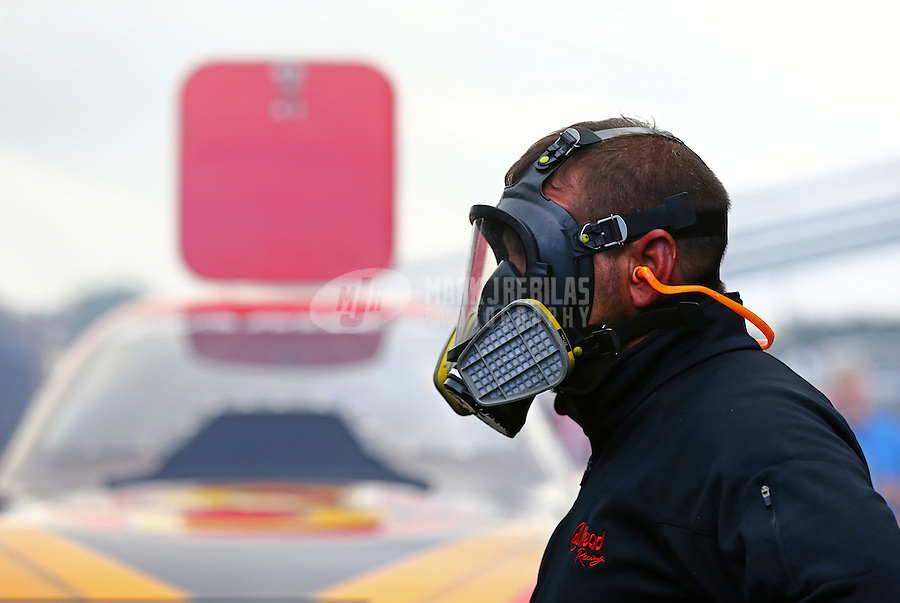 May 18, 2014; Commerce, GA, USA; Jason Wurtzel a crew member for NHRA funny car driver Chad Head (not pictured) wears a gas mask as they warm up the car in the pits during the Southern Nationals at Atlanta Dragway. Mandatory Credit: Mark J. Rebilas-USA TODAY Sports