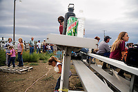 A girl plays with a puppy under the bleachers at the Mechanical Bull-A-Rama at the Whoa Arena in Valier, Montana, USA.  The event, organized by Janelle Nelson, was a benefit for local youth rodeo participants and the local food bank.