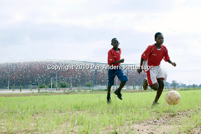 JOHANNESBURG, SOUTH AFRICA - JANUARY 16: Players in a youth team practice on a field in front of Soccer City on January 16, 2010, in Johannesburg, South Africa. These young players practice several times a week and usually have at least one game on the weekend. They are based in Soweto and are struggling with funding for uniforms and balls. Soccer City is the stadium where the opening and final game of the World Cup will be played. Many soccer fans in the country are excited about the upcoming World Cup tournament in June, 2010. (Photo by Per-Anders Pettersson/Getty Images)