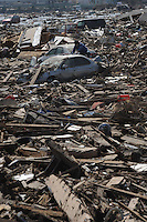 A man looks through the remains of his car that lies amongst the splintered remains of houses in the  town of Natori, after the Tsunami devastated the entire pacifc coastline of Japan after the earthquake and tsunami devastated the area Sendai, Japan.<br />