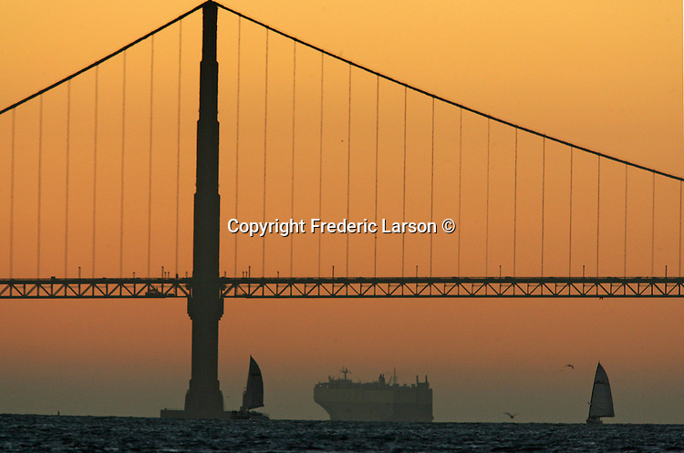 The sun warms the sky behind the Golden Gate Bridge as sale boats and tanker ships paint San Francisco Bay, California.