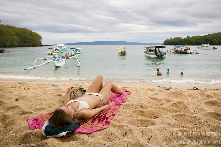 A woman in a bikini lies on a beach while three kids enjoy swimming in the warm waters of Padangbai in Bali, Indonesia. A cloudy sky and fishing boats fill the background.