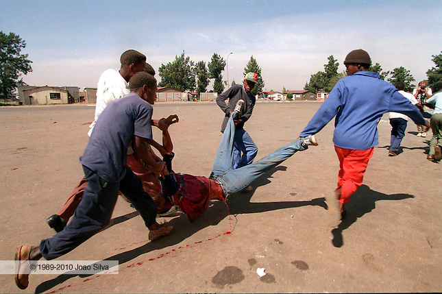 ANC Self Defence Unit members carry a wounded comrade, Bafana Baloyi, spouting blood from a bullet wound in his side during an attack on the Inkatha dominated Mshay'zafe Hostel, Thokoza. April 19 1994.