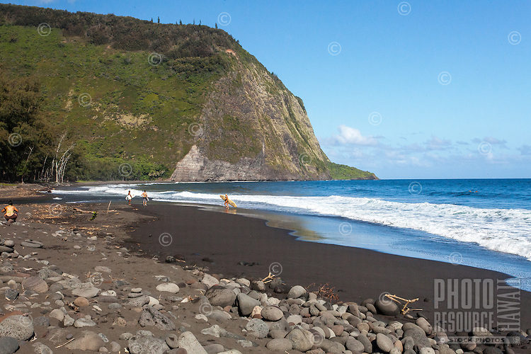 Surfers gathering at the black sand beach in Waipi'o Valley, Big Island.