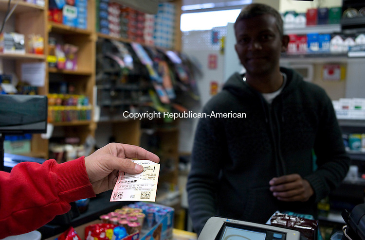 Naugatuck, CT- 12 January 2016-011216CM04- Al Chipelo of Naugatuck buys a quick pick lottery ticket at the Xpress Mart from Joe Alexander in Naugatuck on Tuesday.  Chipelo said if he won the lottery he said that he would pay of family debt and then give to various charities.   Christopher Massa Republican-American