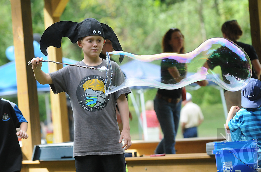 NWA Democrat-Gazette/FLIP PUTTHOFF<br /> BUBBLES AND BATS<br /> Alex Henry 11, makes bubbles on Saturday August 22 2015 during the &quot;Bluegrass and Bats&quot; event at the Illinois River Watershed Partnership property in downtonw Cave Springs. The evening event featured games for kids, fishing, bluegrass music and the chance to see bats emerge from Cave Springs Cave at dusk.