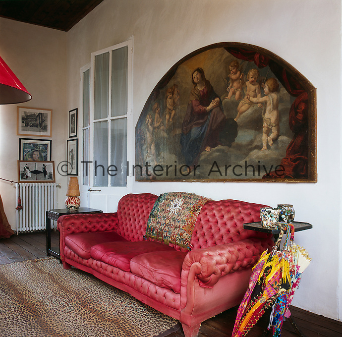 A large painting with religious imagery hangs on the wall above an upholstered pink sofa in a traditional sitting room