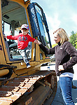 """Torrington, CT 051819MK06 Tara Fischer, from Litchfield,  lends a hand to her son Max as he exits from heavy equipment at the O&G Industries' annual Touch a Truck Family Fun Event at their maintenance facility on Saturday Morning.  Seth Duke, marketing director, said """" With the weather so nice today we will receive over two-thousand attendees and the suggested donations will be donated to Kids Play to help with their continued development.""""  O&G's Jim Zambero, vice president of equipment purchase and maintenance, said that sixty volunteers and twentyfive local vendors helped host the event while members of the Operational Engineer's Union Local #478 directed traffic and managed parking . Michael Kabelka / Republican-American"""